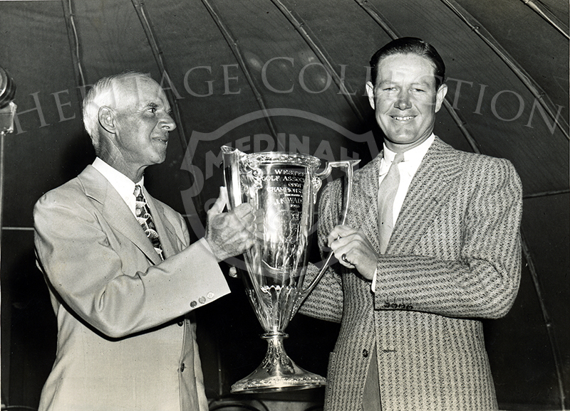 Byron Nelson of Reading, PA. (right) received the trophy from Leslie Cooke, president of the Western Golf Association, after winning the 40th Annual Western Open Golf Championship. Nelson won with a score of 281, two under par for the 72-hole route.