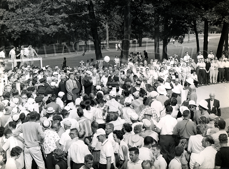 A large crowd surrounded the presentation ceremonies at the conclusion of the 59th Western Open in 1962. In the middle of the scene is Chick Evans, wearing a white cap and holding a microphone in hand. Directly to his left is Arnold Palmer, who finished in seventh place. Standing to the right of the large trophy and directly below a balloon, is Jackie Cupit, who won the tournament with three under par.