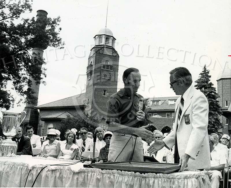 During the 75th U.S. Open award ceremony, Lou Graham, on the left, gets ready to shake hands with Don Stillwaugh, Chairman of the Open. Graham's wife and daughter are seen to the left in the first row, and the Medinah clubhouse is in the background.