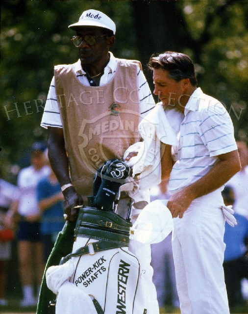 Gary Player, seen with his caddy, shows evidence that the heat didn't let up on Monday, August 9th, during the Ninth U.S. Senior Open Championship playoff round against Bob Charles. Player posted a 68 that day to defeat Charles' score of 70.