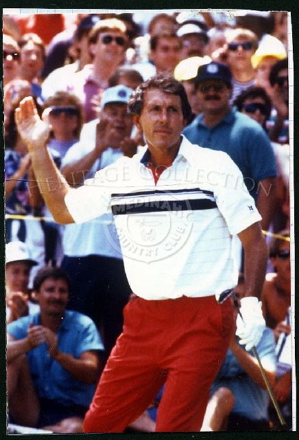 Two-time U.S. Open winner Hale Irwin waves to the fans surrounding the 18th green after sinking a 60-foot putt to put him in the clubhouse at 8-under for the tournament. The scene is from the Fourth Round of the 90th U.S. Open, which was played on Sunday, August 17, 1990