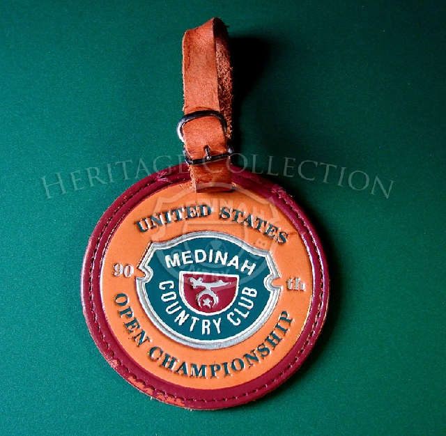 The elegant leather golf bag tag for the 90th U.S. Open, measures 3 1/2-inches in diameter. It includes the official Medinah Country Club logo.