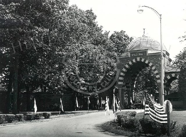 Front gate tower with flags. White Fez- All Nations Day. Aug 4, 1955. Car in scene is a 1950 Pontiac.