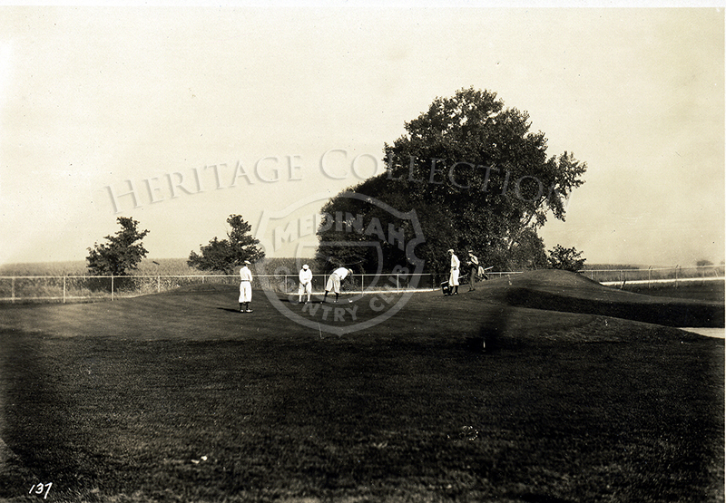 Golfers by sandtrap. Fence in background.