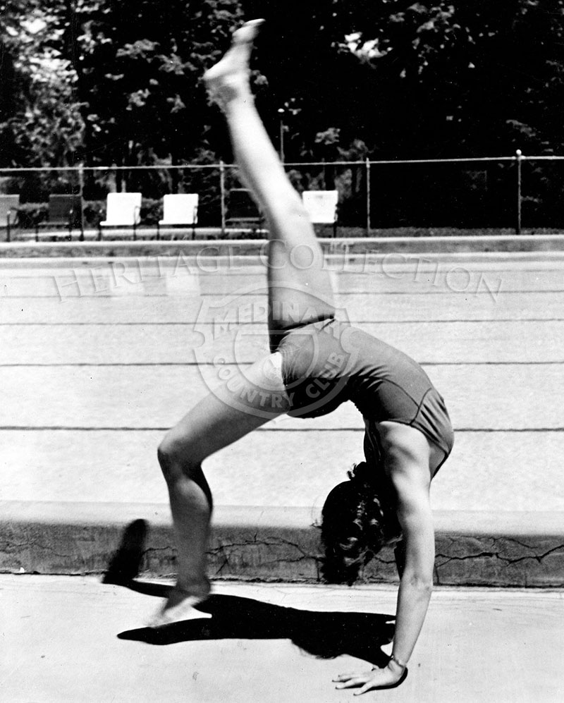 Medinah Country Club's swimmer Lorraine Zeiber doing handstand by the pool.