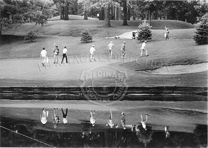 A scenic view of golfers by a sand trap, with water reflection.