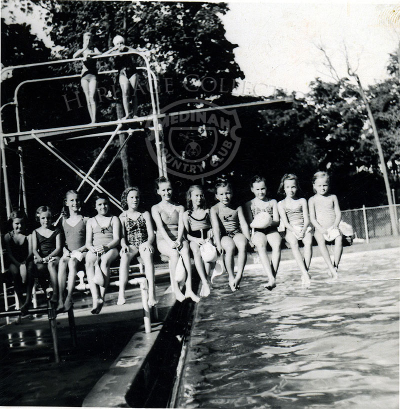 Poolside with 11 girls sitting on springboard.
