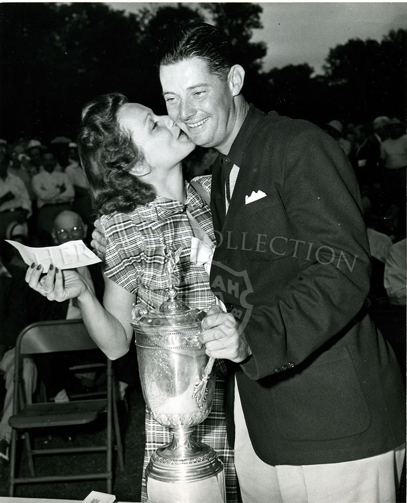Dr. Cary Middlecoff receives a kiss on the cheek from wife Edith, who is also holding up the first place check for $2,000, after Middlecoff won the 49th U.S. Open in 1949.