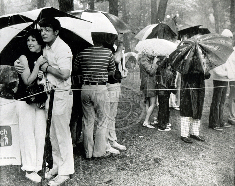 While others huddled under umbrellas and rainwear in the downpour that swept Medinah Country Club, the young lady at left didn't seem to mind the togetherness a bit. The heavy rains cancelled all practice that day for contestants in the U.S. Open.