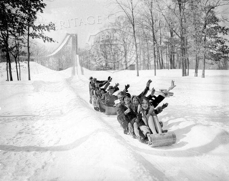 Tobogganing was one of several winter sports offered to Medinah members in 1929. The photograph was shot by the Chicago Daily News, and captured two groups of men and women on toboggans at the end of a snowy run. There were two fast slides in a V-shape on Medinah grounds, one for ski and the other for toboggans. Dating back to 1925, the slides were located west of the 18th tee, on Course No. 3. Medinah was the only country club with a ski jump and toboggan slide. The ski jump was 50-feet in height. Both were taken down in the 1950s. This image is featured in the March, 1929, Vol. 5 No.3 issue of The Red Fez club magazine, on page 16.