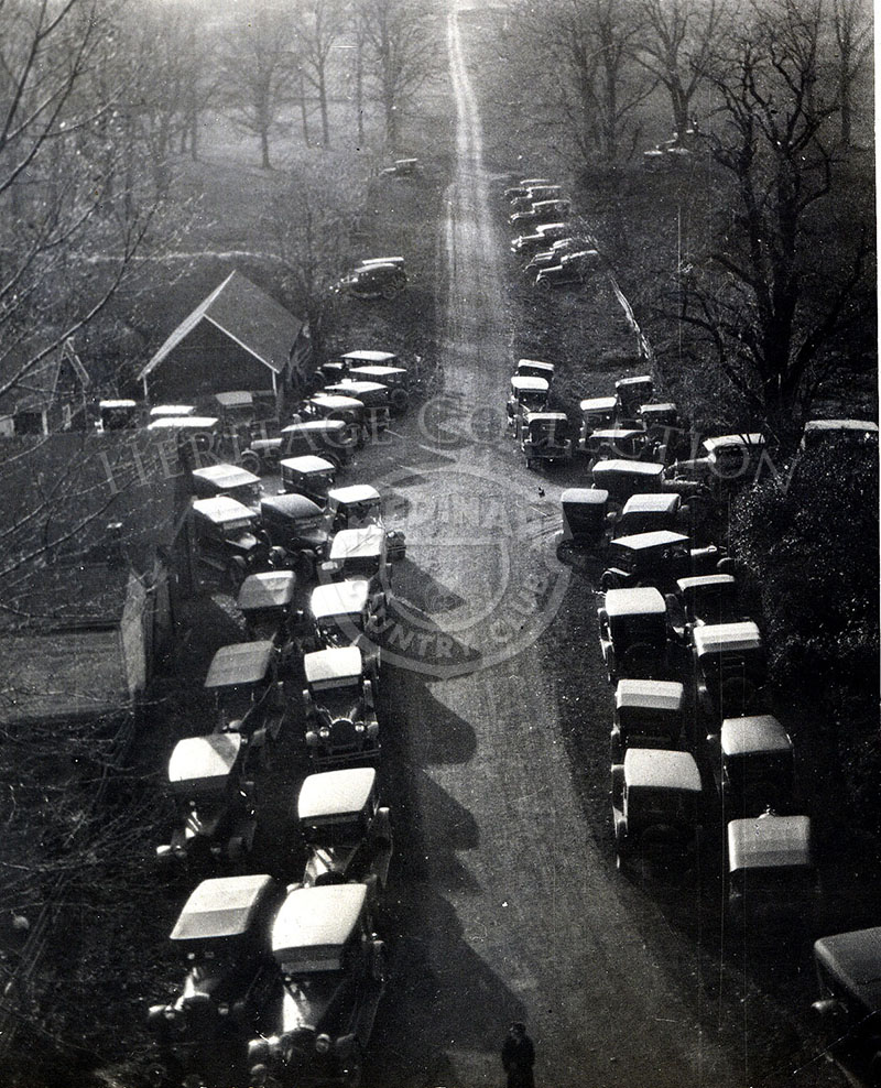 Dozens of automobiles are parked along the narrow dirt path now called Medinah Road. The scene is from the Groundbreaking Day event, Tuesday, September 16, 1924.  Buildings in the scene are on the Broker Farm with a forest of elms, hickories, thornapples, red hawes, crabapples, and giant oaks, some hundreds of years old on the surrounding grounds.