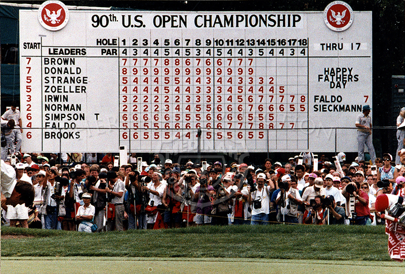 Photographers and golfing fans are tightly packed together near the 90th U.S. Open Leaderboard on Sunday, June 17, 1990. This would have been the Fourth Round of the series. Note the Father's Day greeting on the board, which was celebrated that day. The tournament went into a playoff round the following day between Hale Irwin and Mike Donald. Hale proved victorious.