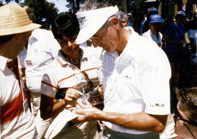 New Zealander Bob Charles signs an autograph for a young fan during the Ninth U.S. Senior Open Championship. At the time, Charles was the Senior Tour's leading money winner and one of the finest left-hander in the game.