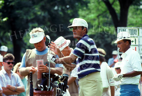 Lou Graham pulls a club from his golf bag during the Ninth U.S. Senior Open Championship in 1988. On the right, with a cigarette in his mouth, is Chi Chi Rodriquez. Graham finished the tournament in 8th place, tying with Al Geiberger. Rodriquez faired better, tying for 6th place with Harold Henning.
