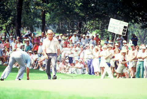 With putter in hand, Arnold Palmer charges on to one of the greens during the Ninth U.S. Open Senior Championship. Note the plaque being carried in the background. It shows that Palmer was grouped with Bob Goalby and Orville Moody. Only Moody finished in
