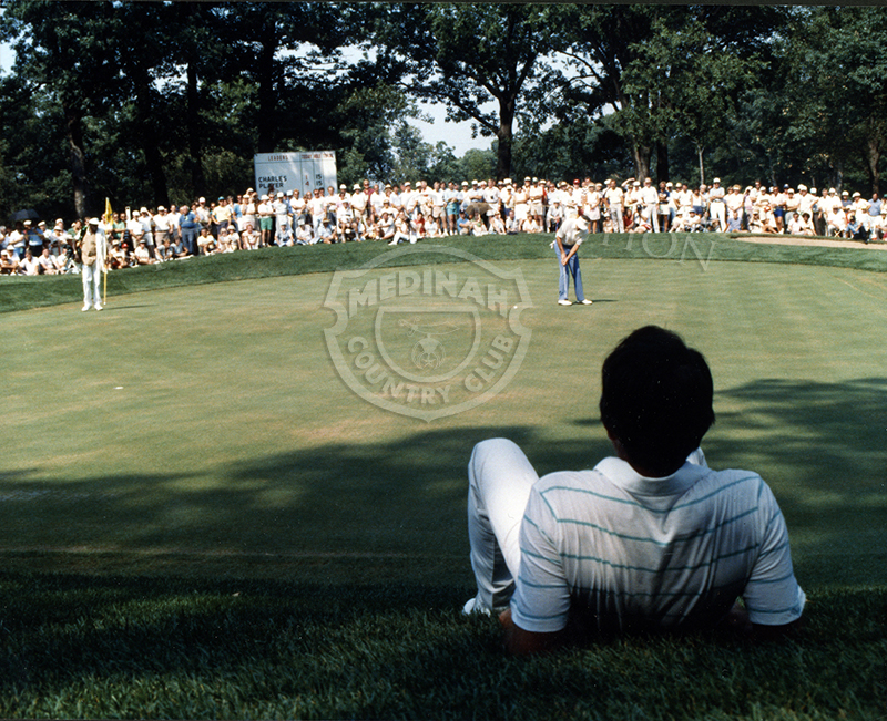 Photograph scene is from the 18-hole playoff round of the Ninth U.S. Senior Open Championship on August 9th. Gary Player, in the foreground, takes a break in the shade as Bob Charles makes a putt on the 15th hole of Course No. 3.  With an estimated 6000 spectators that day, Player went on to defeat Charles by one stroke.