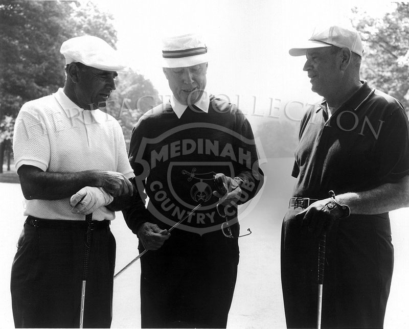 Chick Evans in the center, discussed a golf club with two other gentlemen during the 63rd Western Open. Evans won the Open 56 years earlier.