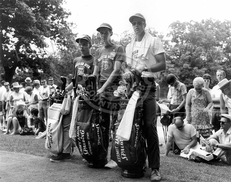 Three young men await the pros they will caddie for during the 63rd Western Open. From left to right, first caddie holds the golf bag for Walter Hagen. Middle bag was for Tommy Aaron, and Kermit Zarley's bag is on the right.