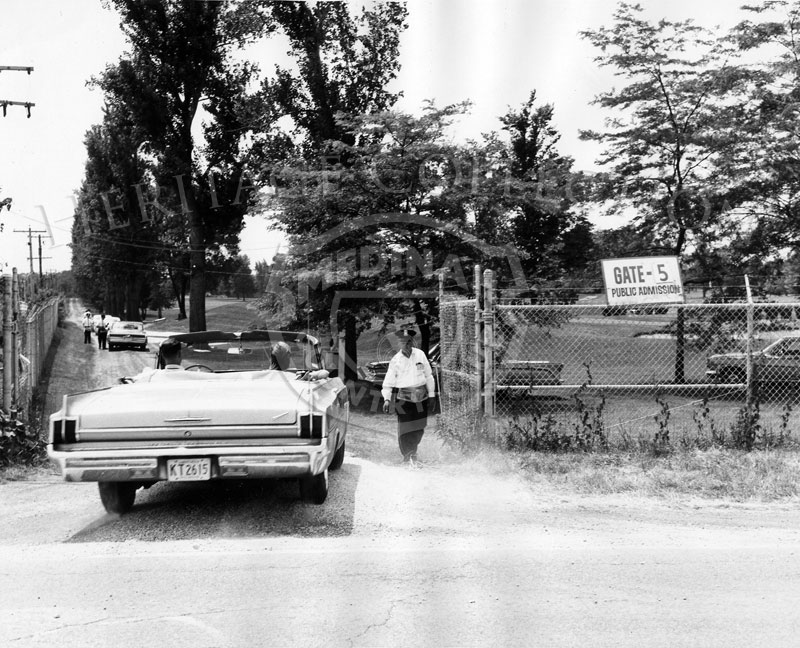 A 1963 Oldsmobile convertible is seen driving off of Illinois Route 19, Irving Park Road, and through one of the public entrance gate onto Medinah Country Club property for the 63rd Western Open in 1966.