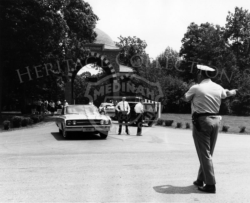 Local police and Andy Frain ushers coordinated efforts to keep traffic flowing in and out of Medinah Country Club's main entrance gate during the 63rd Western Open. A 1964 Oldsmobile is coming out the entrance and onto Medinah Road.