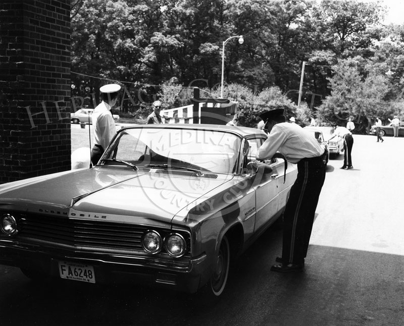 Andy Frain ushers verified Medinah Country Club members' credentials at the main entrance gate during the 63rd Western Open. The car in the photo is a 1963 Oldsmobile two-door hardtop.