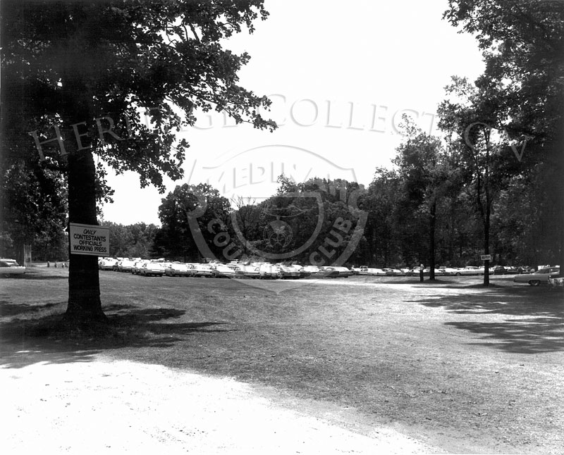 A wide shot of one of the many parking areas on Medinah Country Club grounds, used during the 63rd Western Open tournament in 1966. A sign on the tree to the left in the foreground reads,