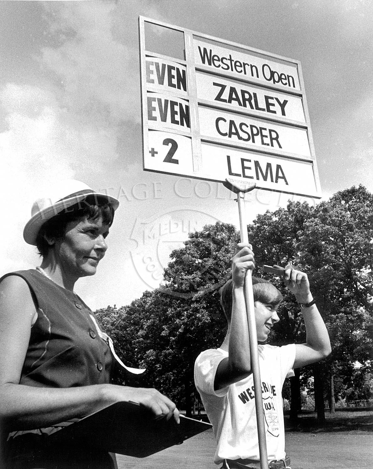 The sign held by the young man during the 63rd Western Open was for the golf trio of Kermit Zarley, Billy Casper and Tony Lema. Casper went on the win the tournament with a total score of 283, which was one under par.