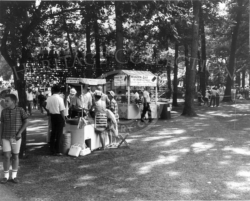 Examples of small refreshment booths are pictured during the 63rd Western Open tournament in 1966. In the foreground is a stand for Mazzone's Fruit Ices, and directly behind, is a larger booth for Wonder Bar Ice Cream on a Stick. The sign informs that this treat was