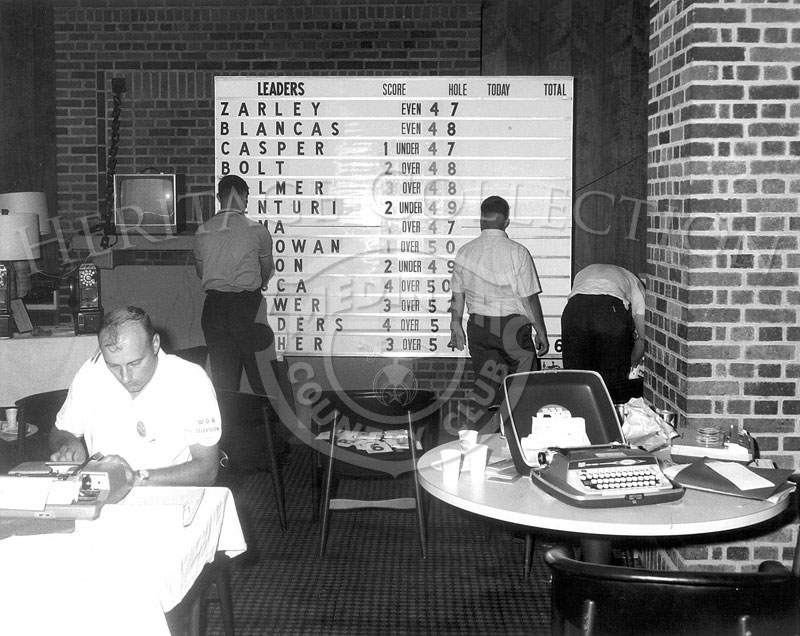 The media room, with working members of the press, was located inside the Medinah Club House. Portable typewriters were used to compose articles and reports during the 63rd Western Open tournament in 1966. Similar to the Leader board outside on Course No. 3, there was one in the media room to visually keep up to date on the standings. The armband on the gentleman in the foreground specifies that he was a member of the WGA Television media.
