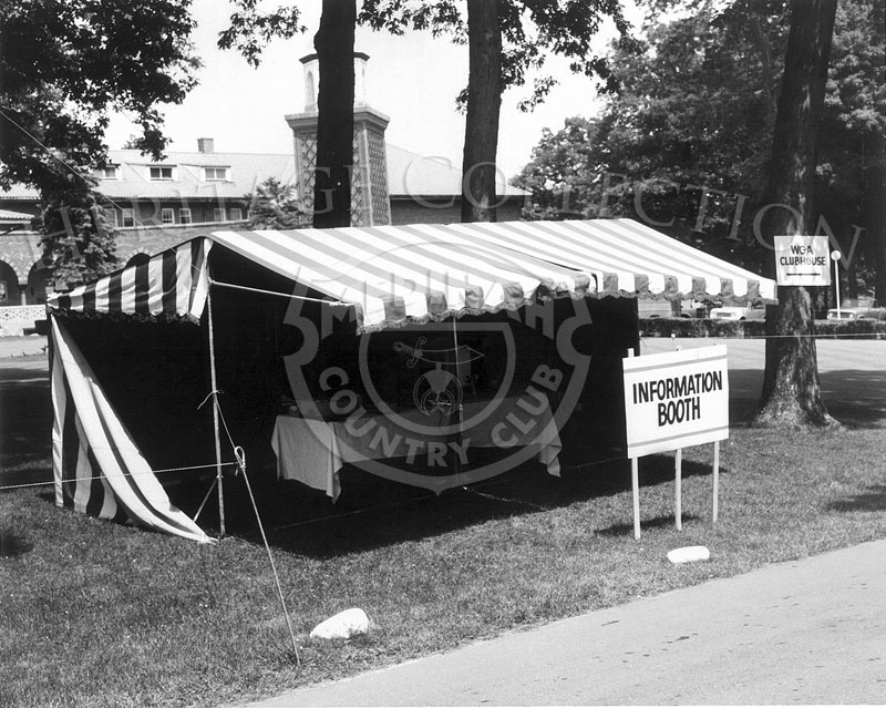 An Information Booth was set up on the lawn in front of the Medinah clubhouse. In the background, sections of the historic building can be glimpsed, including the South Tower.