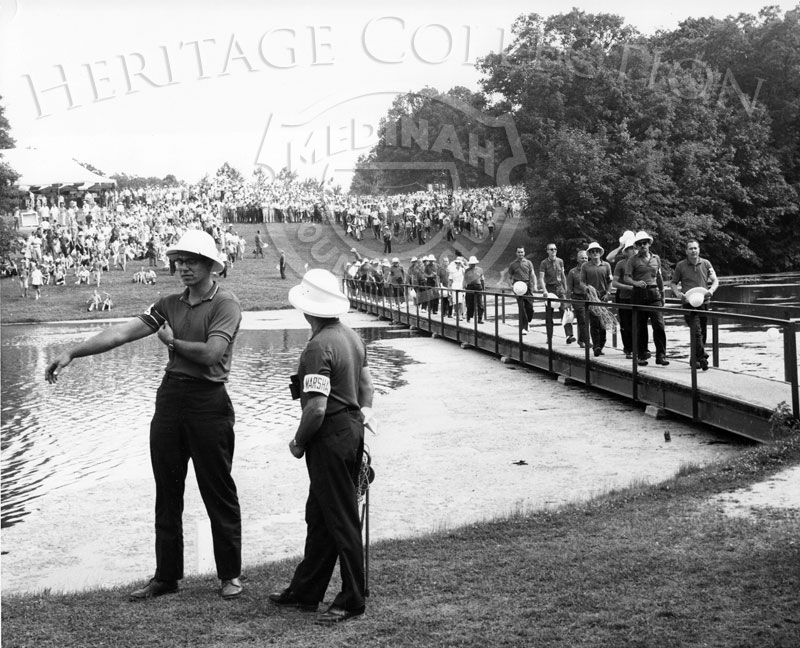 Tournament Marshals are pictured in the foreground and crossing one of the foot bridges that span over Lake Kadijah during the 59th Western Open.