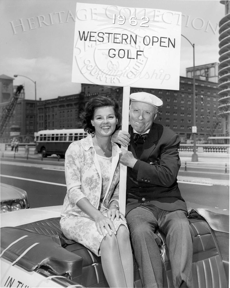 American singer and former beauty queen Anita Bryant and legendary amateur golfer Chick Evans appeared in a parade to promote the 59th Western Open tournament at Medinah. This scene was photographed on Wacker Drive in Chicago, with a portion of Marina Towers on the far right. The Evans Scholars Foundation is named for Chick Evans, who founded the scholarship organization that is supported by the Western Golf Association.