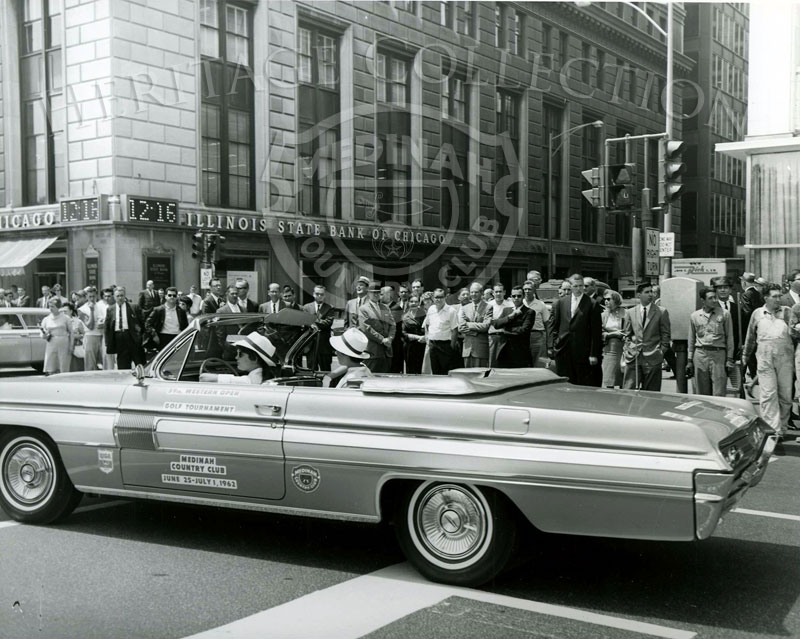One of several Oldsmobile Starfire convertibles used as Official Cars during the 59th Western Open is pictured on Michigan Ave. The photo was taken during a parade to promote the golfing event held at Medinah Country Club in 1962.