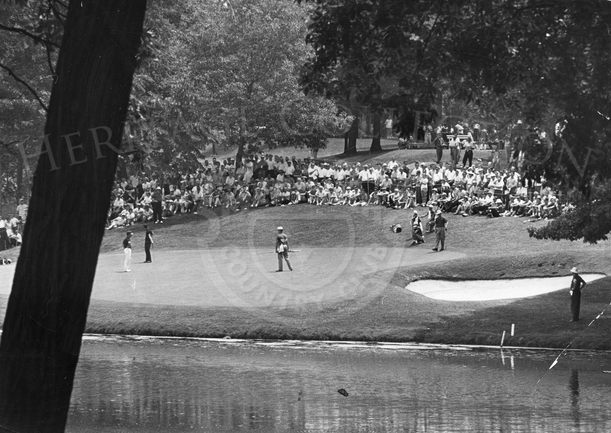 Scenic view over Lake Kadijah to the 2nd green during the 1962 Western Open. Jacky Cupit, Gary Player, and Harold Kneele are the players on the green June 30, 1962