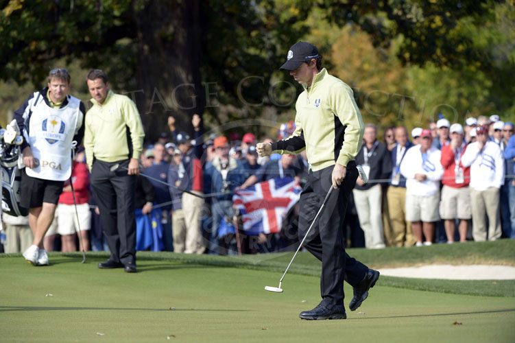 Rory drains his putt while partner Graham McDowell watches on the 8th hole on Friday.