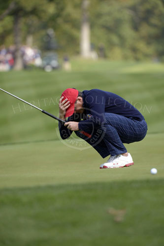 Bradley crouches in disbelief as his putt for birdie just misses on the 14th hole.