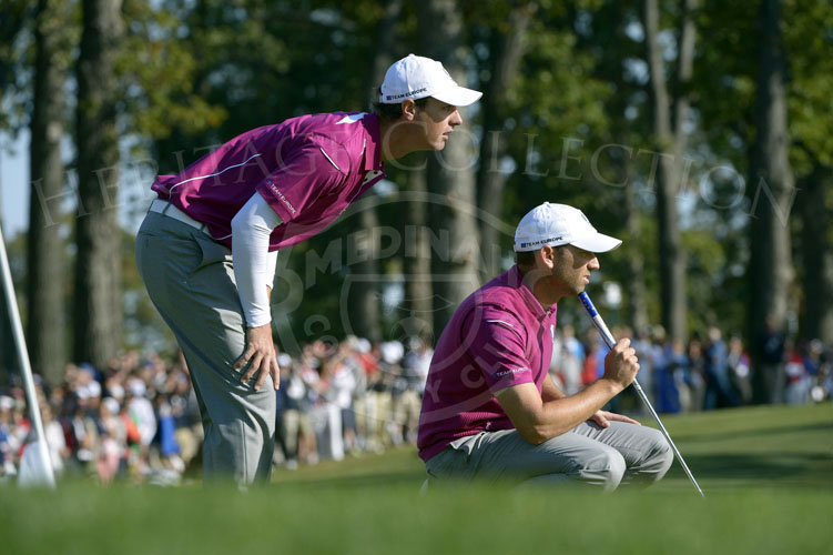 Teammates Colsaerts and Garcia check the movement of the putt on the 8th green.