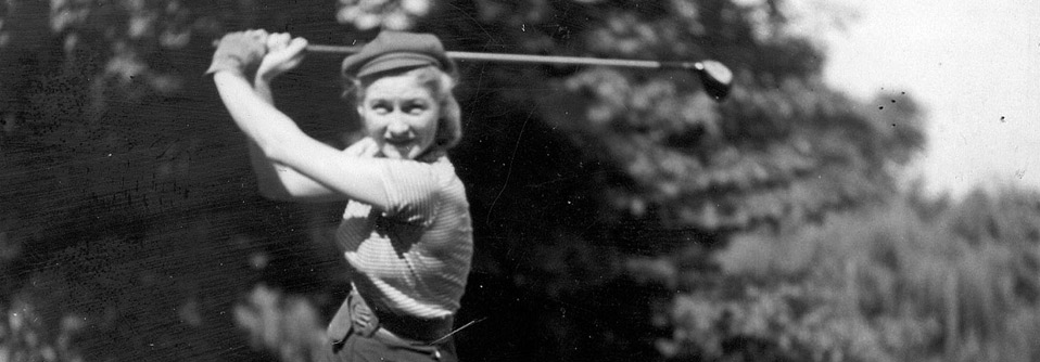 A woman poses with a golf club on the course at Medinah