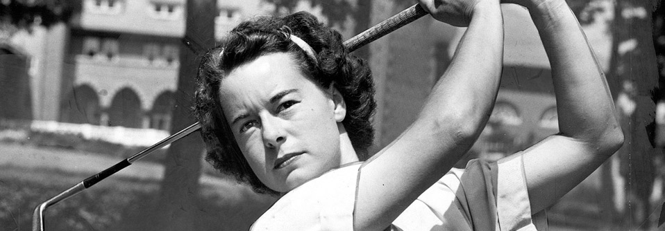 Betty Hicks swings a club in front of the Medinah Clubhouse
