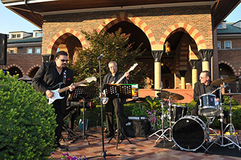 Rock band playing music on the patio outside of the Clubhouse